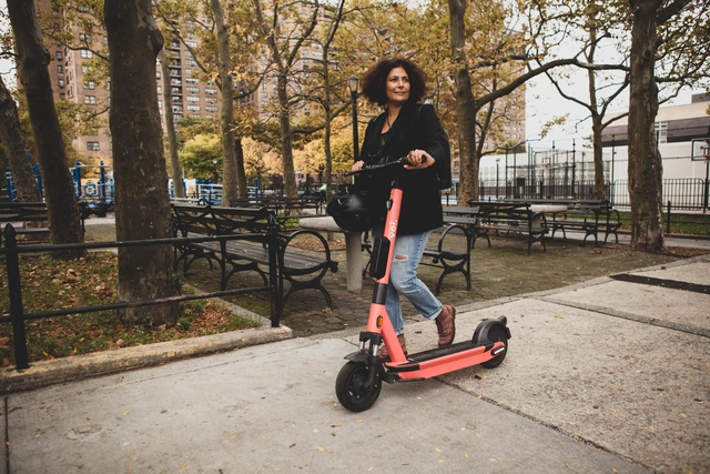 woman walking with a voi e-scooter in New York City