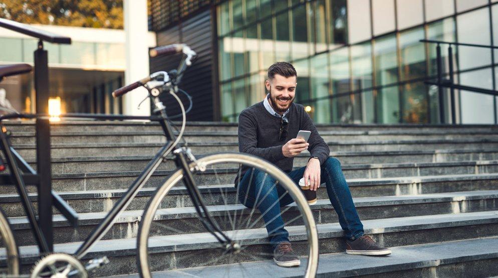 En person som använder mobilen när han sitter på trappan | KFX