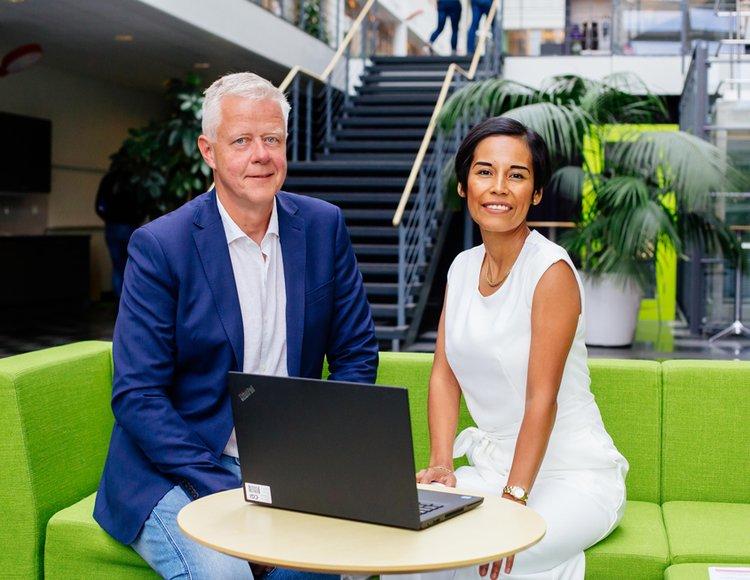 Carol Lundqvist sitter på en grön soffa tillsammans med sin chef Anders Löfgren.