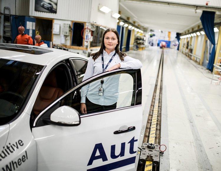 Projektingenjören Hanna ståendes bredvid en testbil i den stora verkstaden.