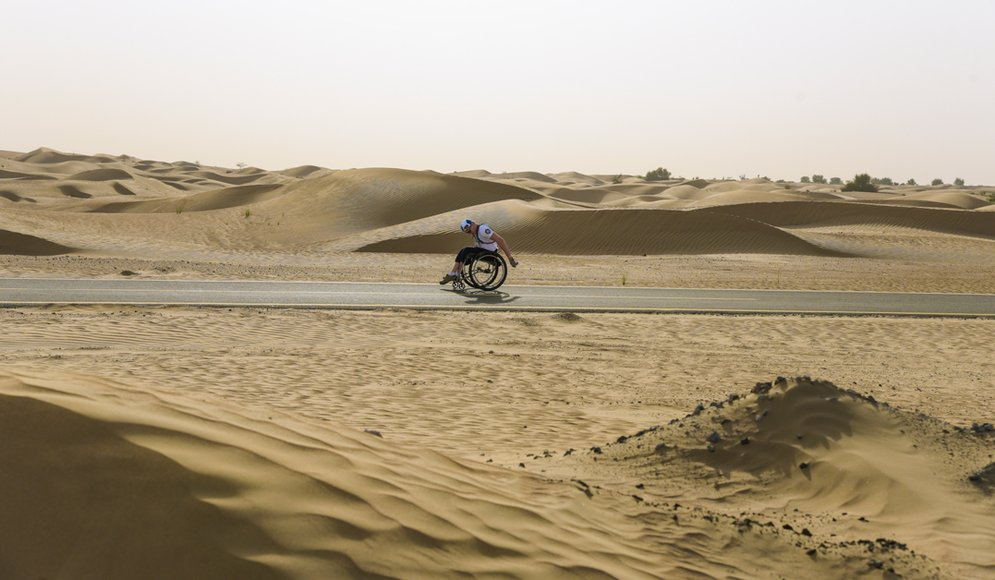 Aron Andersson kör sin rullstol genom ett ökenlandskap.