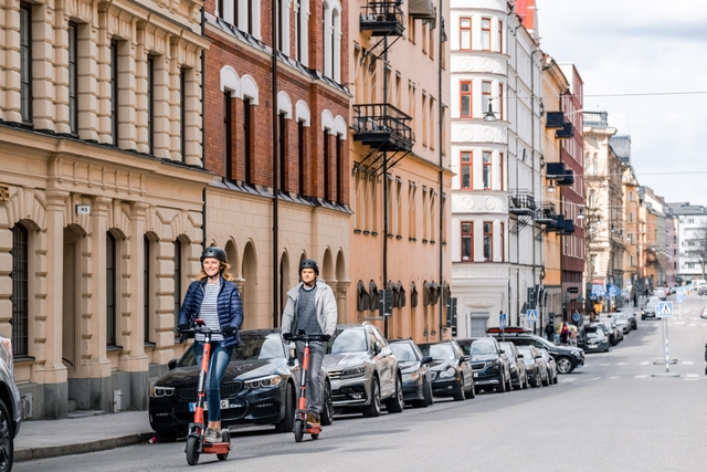 woman and man riding voi e-scooters on a street in Stockholm