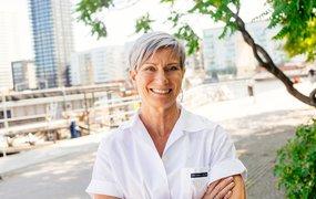 Liza Nyberg på Svensk Fastighetsförmedling står i skuggan av ett träd med en byggarbetsplats i bakgrunden.
