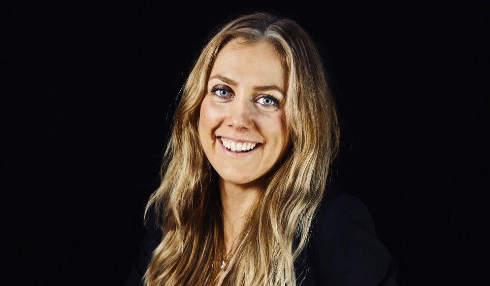 Carolin Solskär sitter vid ett bord i en studio med svart bakgrund.