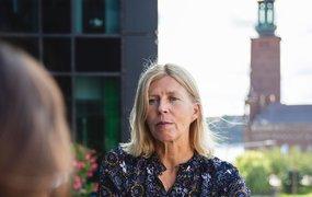 Sirpa Rusanen på Svensk Exportkredit står utomhus och pratar med en kollega. I bakgrunden syns stadshuset i Stockholm.