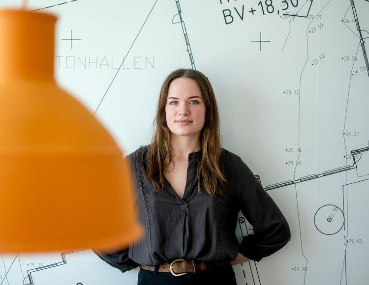 Civilingenjören och soldaten Agnes Tyrén står lutad mot en vägg som föreställer någon slags ritning. Hon tittar in i kameran. I förgrunden syns en gulorange taklampa.