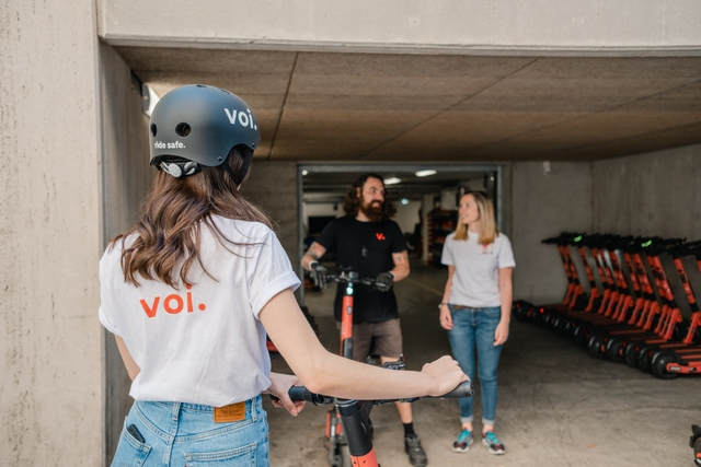 A woman in a helmet standing in front of a Voi warehouse in a white t-shirt with the Voi logo on the back
