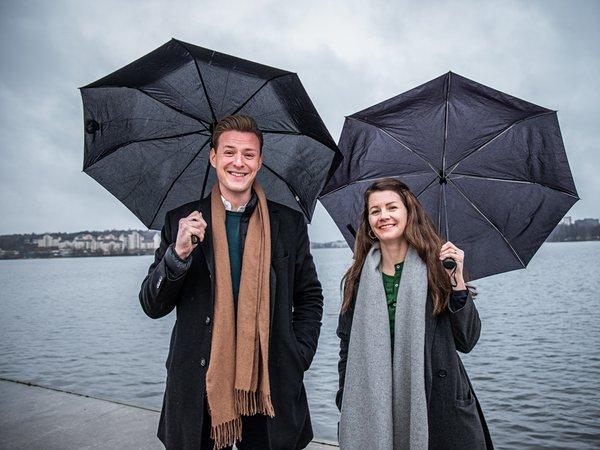 Ida Landin och Jonas Lundgren står utomhus under varsitt paraply med vatten i bakgrunden.