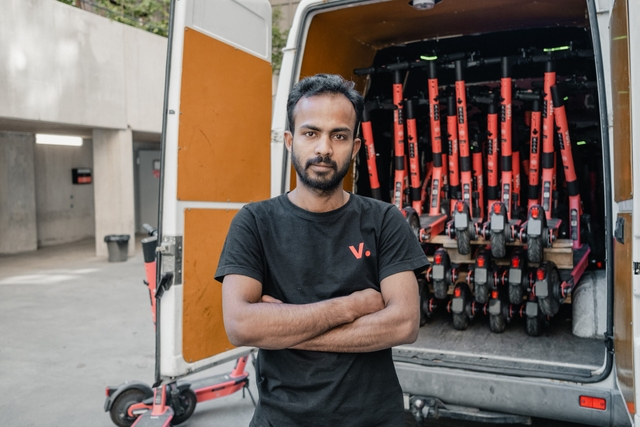 A Voi employee in front of a van full of e-scooters.