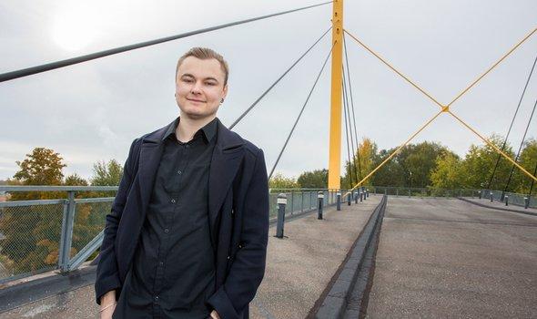 Daniel Bond står utomhus på en gångbro.