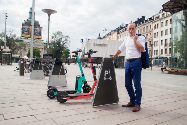 a green and a red e-scooter parked in a rack, a man is standing next to the rack with his right hand on it