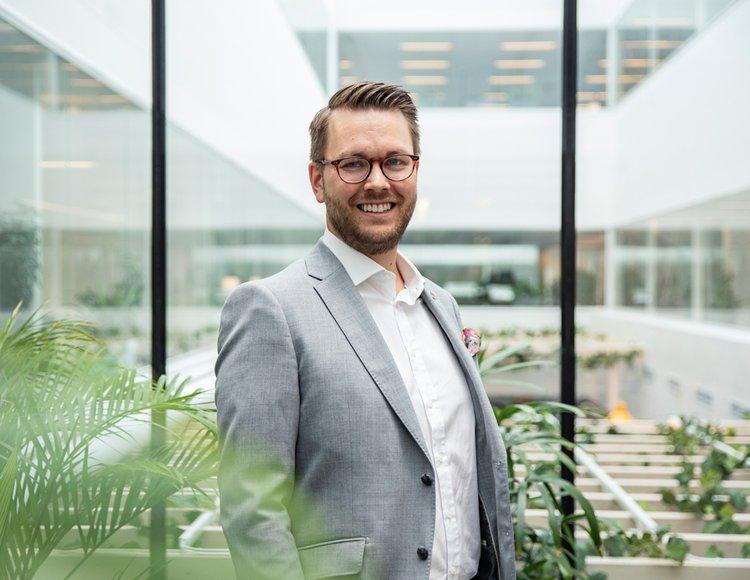 Richard Orgård, HR- och hållbarhetschef på Securitas står i den växt täta ljusgården på huvudkontoret klädd i ljus kostym och vit skjorta.