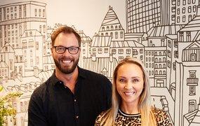 Ulf Häger, rekryteringsansvarig och Linda Nyström, tf. HR-chef. På väggen bakom syns en skiss över en stadsdel i svart och vitt.