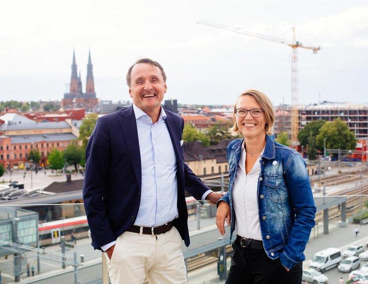 Anna Bittner, HR-direktör och kollegan Joachim Danielsson, stadsdirektör ler in i kameran. I bakgrunden breder Uppsala stad ut sig, båda nybyggnationer och den ikoniska domkyrkan.