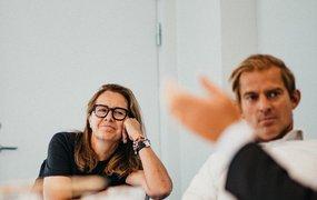 Charlotte WWibe, Director HR Workplace & Service sitter lutandes på en stol tillsammans med kollegor  i ett av TUI:s mötesrum.