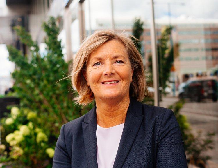 Almis HR-direktör Eva Ottne står utanför entrén klädd i kavaj och vit blus.
