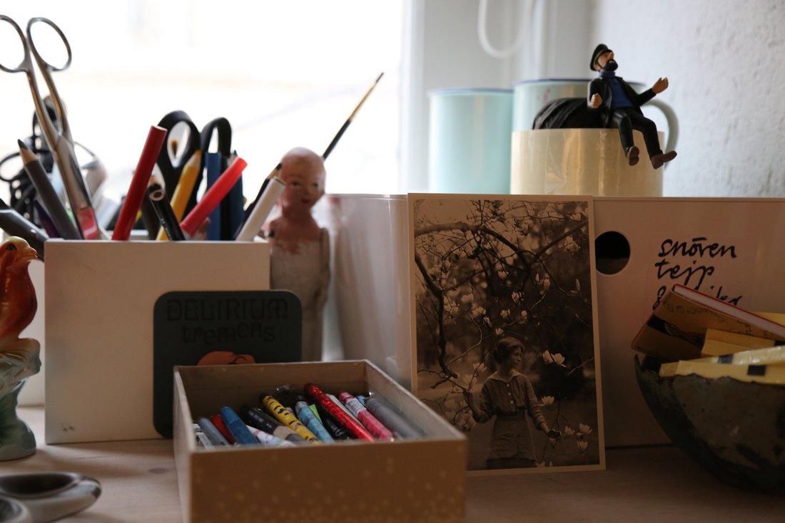 På hyllan ovanför Stina Wirséns arbetsplats ryms pennor, foton och småprylar.