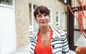 Pia Sandvik, vd på forskningsinstitutet RISE står på huvudkontorets innegård klädd i svart och vit randig kostym över en orange överdel.