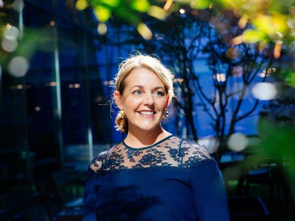 Anna Berggren står, iklädd en blå topp, i ett stort rum med grönska runt sig.