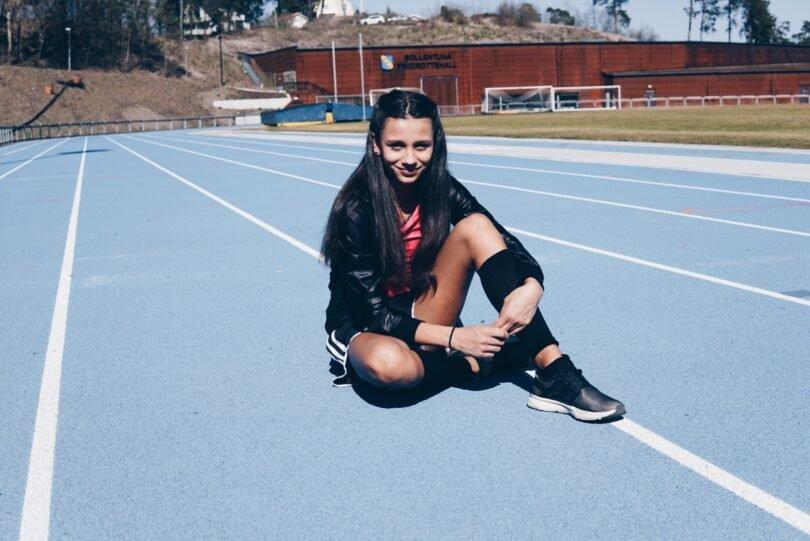 Flicka sitter på idrottsplan