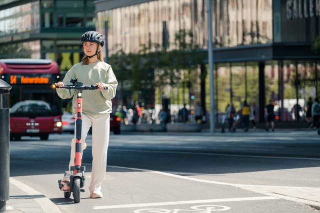 blonde woman in a helmet and grey clothes is standing behind a red e-scooter waiting by an intersection, a bus is driving in behind her