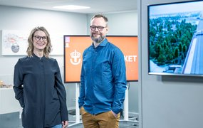 Lena Hägg och Kristofer Södergberg står i en av Trafikverkets lokaler med två stora skärmar i bakgrunden.